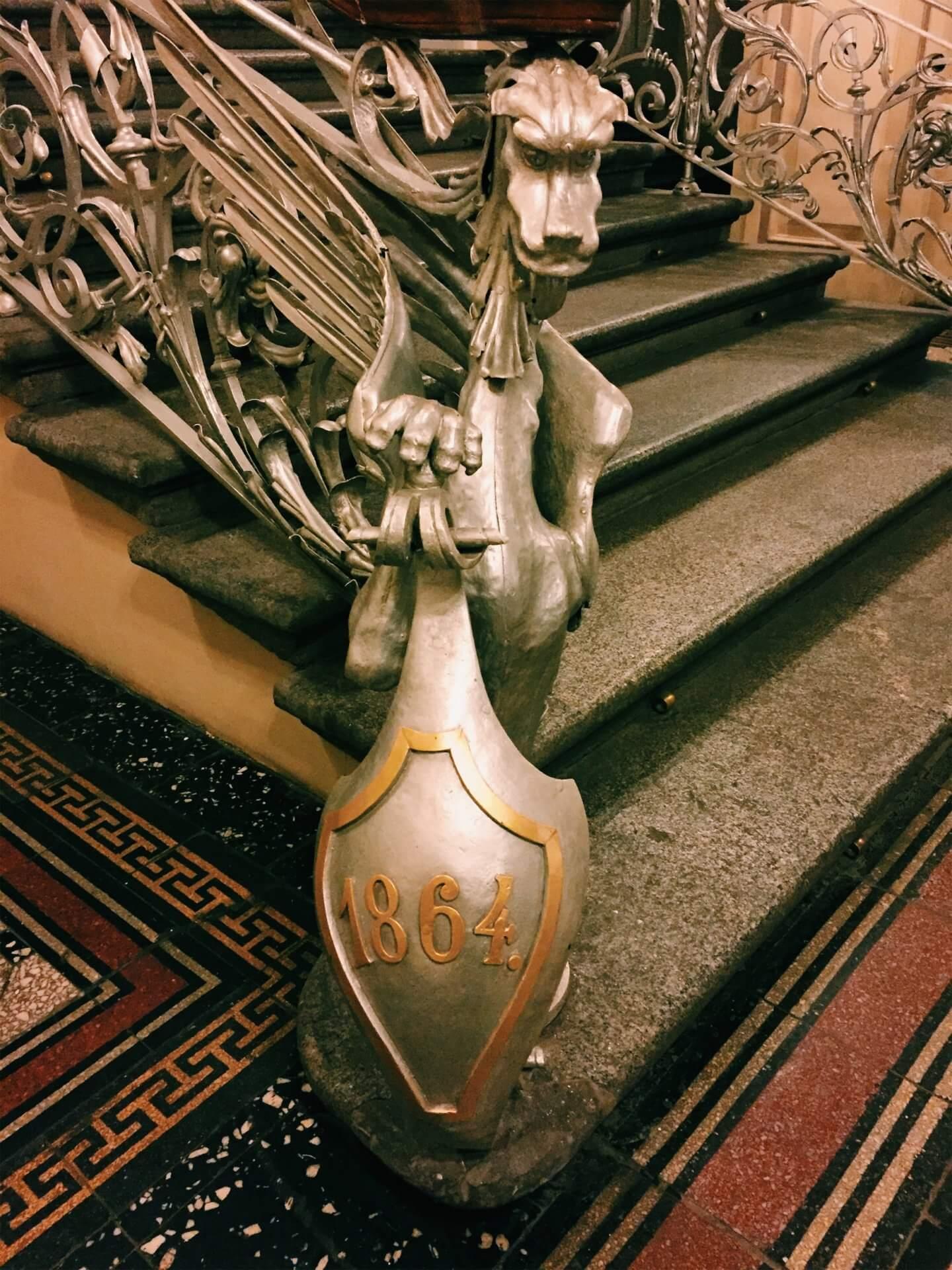 Дракон на лестнице держит щит с датой начала функционирования общества
